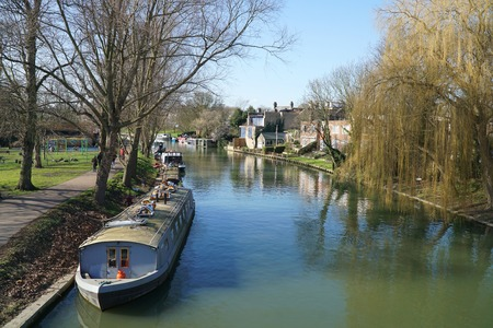 CAMBRIDGE, UK - FEBRUARY 24 2016: People walk along a riverside path along the boat lined banks of the River Cam, Cambridge, England on a sunny winter's day.
