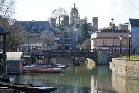 CAMBRIDGE, UK - FEBRUARY 24 2016: Tourists punt down river and pedestrians walk down Bridge Street in the historic centre of the university city of Cambridge, England. Editorial