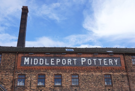 STOKE-ON-TRENT, UK - MARCH 29 2016: A chimney rises behind the main building of the Middleport Pottery works in Burslem, Stoke-on-Trent, in side view as seen from the adjacent public footpath.