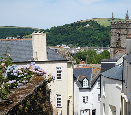 Picturesque view of historic houses, old church steeple, rustic wall and hilly landscape in the coastal British town of Dartmouth, Devon Stock Photo