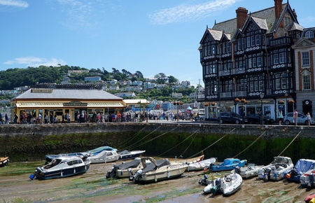 Small boats in harbour at low tide, tourist cafe, crowds of people and a large black and white building on a summer day in Dartmouth, Devon.