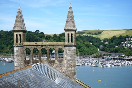 The distinctive spires of St Barnabas Church in the popular tourist town of Dartmouth, England overlook a scenic vista of rolling hills and a busy marina on the estuary of the River Dart in the South Hams, Devon.