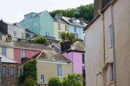 Colourful exterior paint brightens a group of houses on a hillside in the British coastal town of Dartmouth, Devon.