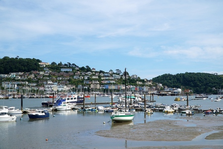 Small boats moored at low tide on the River Dart, Dartmouth, near estuary sand banks, with the village of Kingswear in the background.
