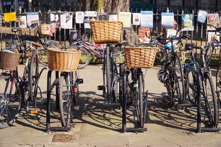parked bikes: CAMBRIDGE, UK - MARCH 13 2016: Parked bikes line the pavement in the centre of the university city of Cambridge, England.