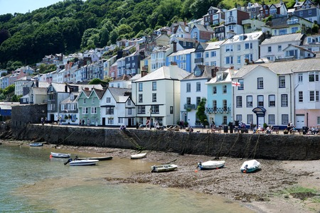 DARTMOUTH, UK - JULY 6 2016: People sit and walk on the riverside promenade in the popular tourist town of Dartmouth, in Devon, south-west England.