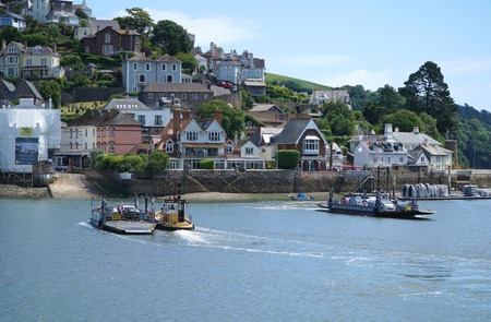 DARTMOUTH, UK - JULY 6 2016: Paired car ferries, pulled by tugs, cross the River Dart between the town of Dartmouth on the western bank and the village of Kingswear on the east.