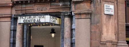 LONDON, UK - JULY 25 2016: The 20th-century styling of the traditional entrance sign of the London's Picturehouse Central arthouse cinema contrasts with the historic columned facade of the building in which it is housed. Editorial