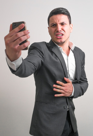 dissapointed: Young business man looking his phone and having dissapointed expression