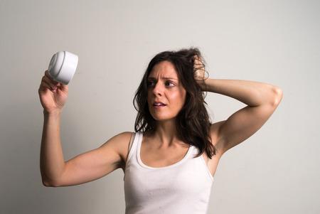 cabeza abajo: Mujer caucásica que sostiene la taza de café al revés con mirada confusa