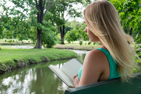 reading book: Beautiful blonde woman reading book in the park Stock Photo