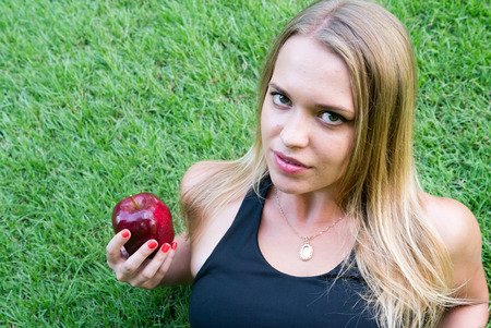 woman laying down: Young blonde woman laying down on the grass and holding red apple in her hand