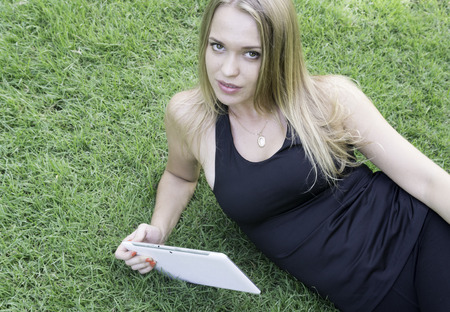 laying down: Beautiful blonde laying down on the grass and holding tablet Stock Photo