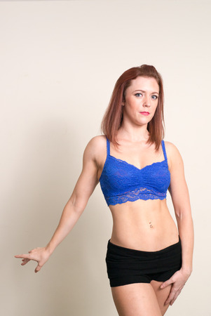 tight body: Red headed fitness girl showing her beautiful body wearing blue top and tight black fitness shorts
