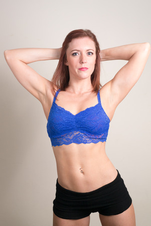 abdominal muscles: Sexy young red head fitness girl holding hands behind her back while exposing her strong six pack abdominal muscles