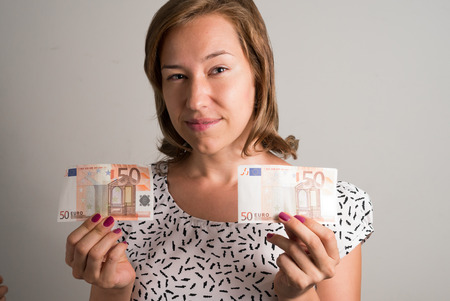 50 euro: Woman holding 50 euro bills in her both hands