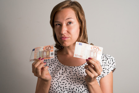 50 euro: Woman holding 50 euro bills in her both hands and thinking what to buy Stock Photo