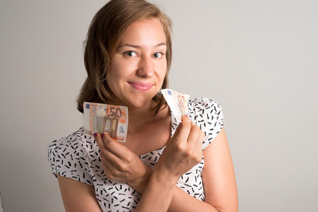 50 euro: Woman holding 50 euro bills in her both hands horizontal studio shot