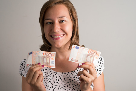 50 euro: Woman holding 50 euro bills in her both hands and smiling Stock Photo