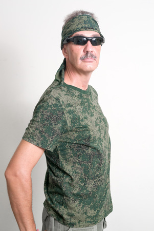 only one senior adult man: Older Caucasian man with mustache wearing soldier outfit ready to airsoft action Stock Photo