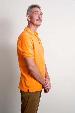 empleadas domesticas: Hombre caucásico mayor con bigote usando la camisa naranja vertical, tiro del estudio