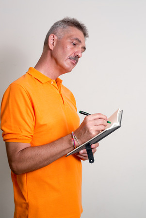 one mature man only: Older Caucasian man with mustache wearing orange shirt and writing to diary vertical studio shot