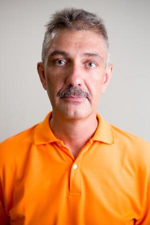 one mature man only: Older Caucasian man with mustache wearing orange shirt vertical studio shot