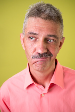 qualified worker: Older Caucasian man with mustache thinking against yellow background