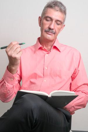 empleadas domesticas: Hombre mayor con bigote sentado y sosteniendo la pluma con el libro vertical, tiro del estudio Foto de archivo