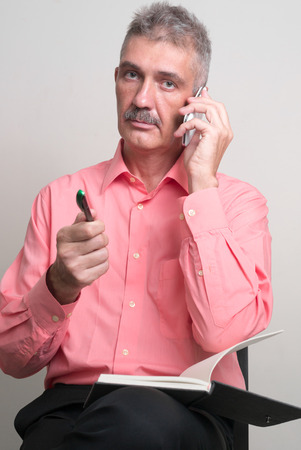 one mature man only: Older man with mustache sitting while talking on the phone and holding pen with book vertical studio shot Stock Photo