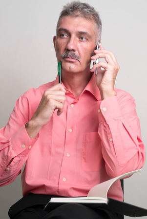 only one senior: Older man with mustache sitting while talking on the phone and holding pen with book vertical studio shot Stock Photo