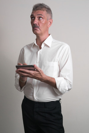 one mature man only: Older man with mustache wearing casual business style and using tablet computer vertical studio shot