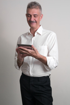 only seniors: Older man with mustache wearing casual business style and using tablet computer vertical studio shot