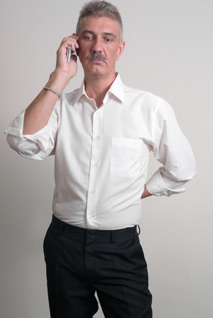 one mature man only: Older man with mustache wearing casual business style and talking on the phone vertical studio shot