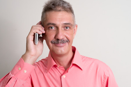 one mature man only: Older man with mustache talking on phone horizontal studio shot