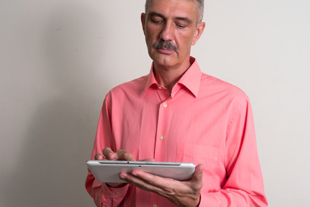 one mature man only: Older man with mustache using tablet computer horizontal studio shot Stock Photo
