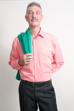 only seniors: Older Caucasian man with mustache wearing colorful shirt and holding green shirt vertical studio shot
