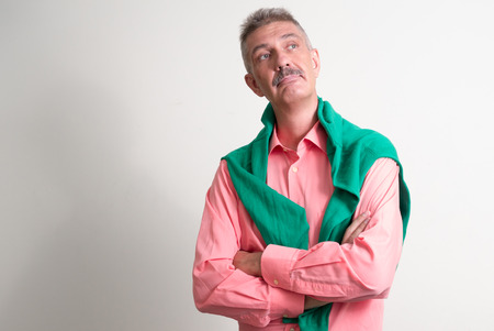 one mature man only: Older Caucasian man with mustache wearing colorful shirt and holding green shirt horizontal studio shot Stock Photo