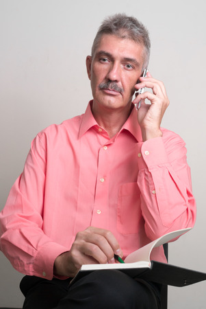 one mature man only: Older Caucasian man with mustache holding pen and book while talking on the phone vertical studio shoot Stock Photo