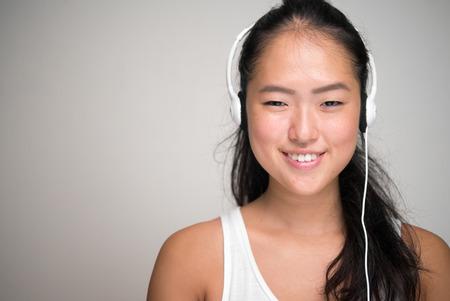 chinese ethnicity: Young beautiful woman from Chinese ethnicity using headset horizontal studio shot Stock Photo