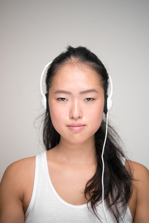chinese ethnicity: Young beautiful woman from Chinese ethnicity using headset vertical studio shot