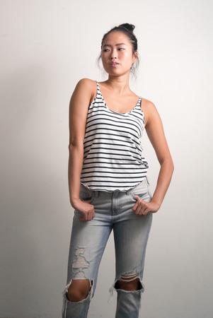 etnia: Hermosa mujer joven de la etnia china que se coloca vertical, tiro del estudio Foto de archivo