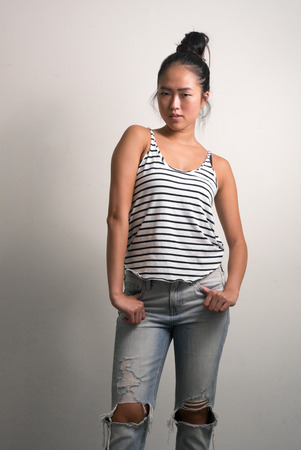 chinese ethnicity: Young beautiful woman from Chinese ethnicity standing vertical studio shot