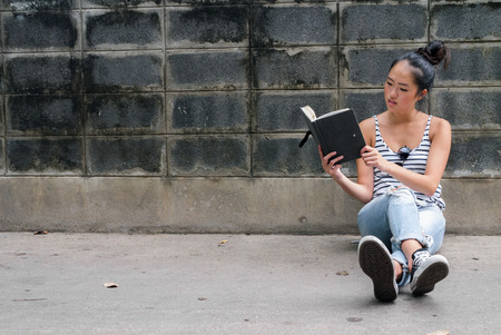 reading book: Young beautiful Asian woman sitting outdoors and reading book Stock Photo