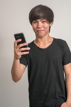 filipino adult: Portrait of young Asian man using smart phone