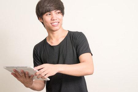 filipino adult: Portrait of young Asian man using digital tablet