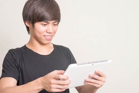 filipino adult: Young Asian man using digital tablet