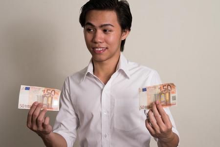 50 euro: Young Asian man holding 50 euro bill