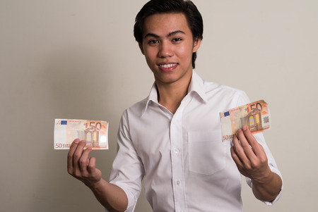 50 euro: Young Asian man holding 50 euro bill