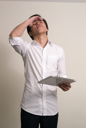dissapointed: Portrait of young Asian man using digital tablet